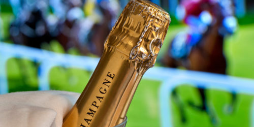 EYX2N3 Close view on champagne bottle in cooler with Royal Ascot Ladies Day horse racing in background Ascot Berkshire UK
